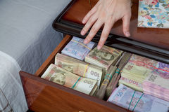 hand-reaches-money-bedside-table-filled-ukrainian-cash-48850037