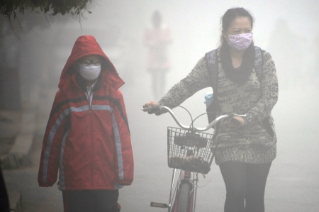A woman walks with her child on a street as schools were closed due to the heavy smog in Jilin, northeast China's Jilin province on October 22, 2013. Thick smog enveloped China's northeast area for a third day on October 22.   CHINA OUT     AFP PHOTO        (Photo credit should read STR/AFP/Getty Images)